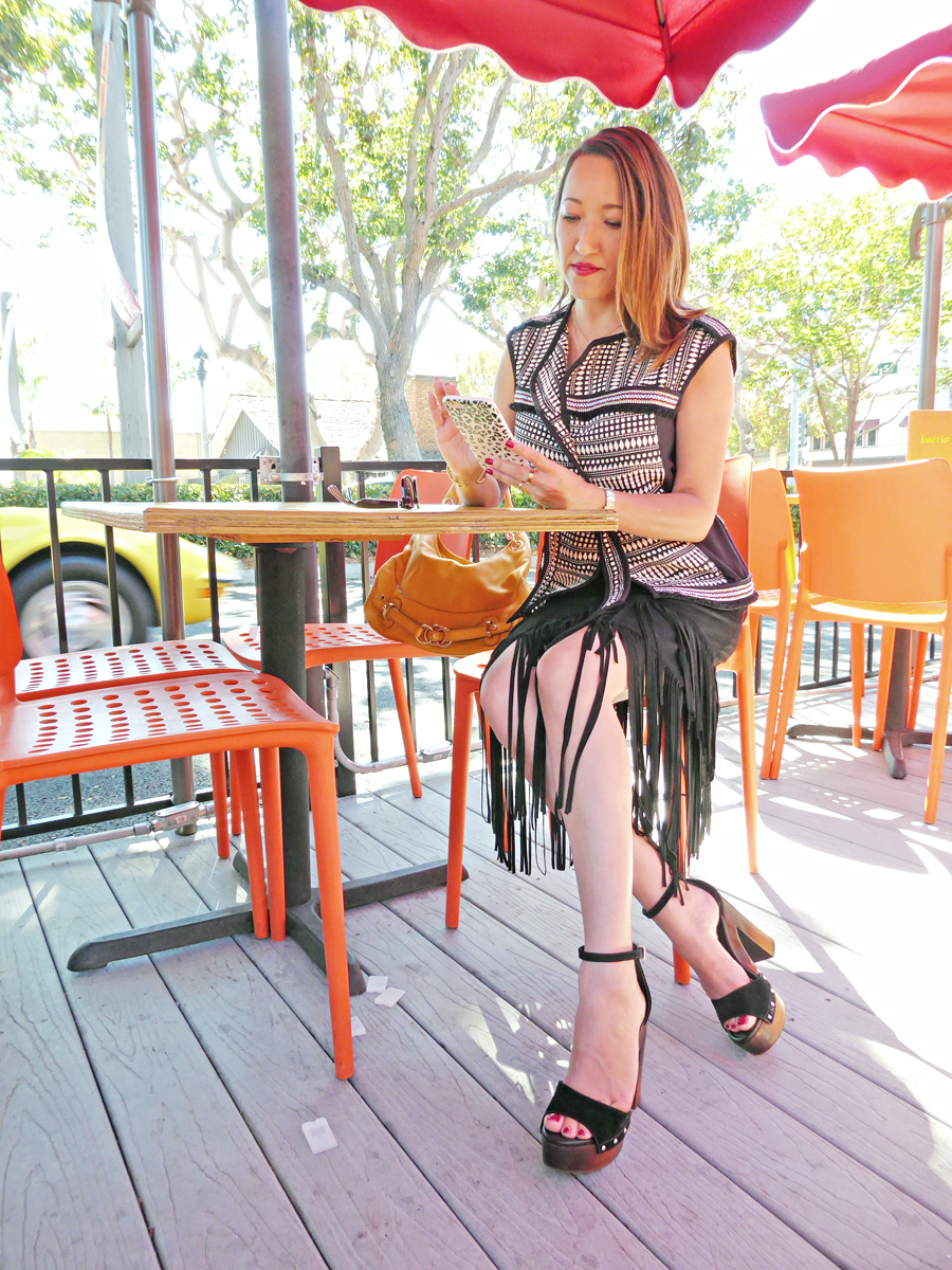 savvynista style at cafe in fringe suede skirt
